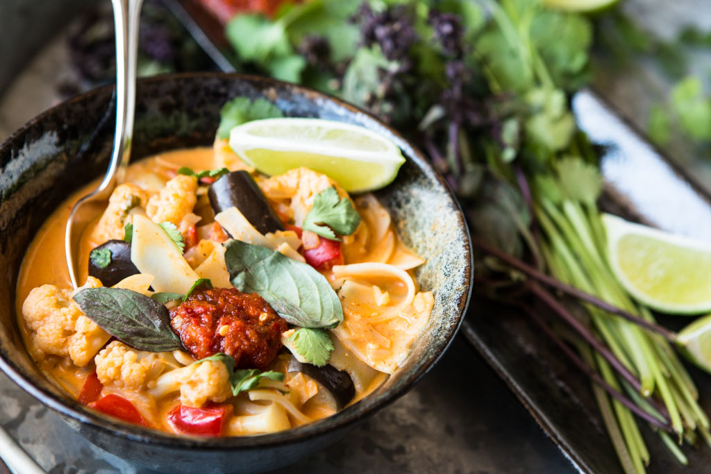 A hot bowl of Thai red curry noodle soup with eggplant and cauliflower – nutritious and delicious.